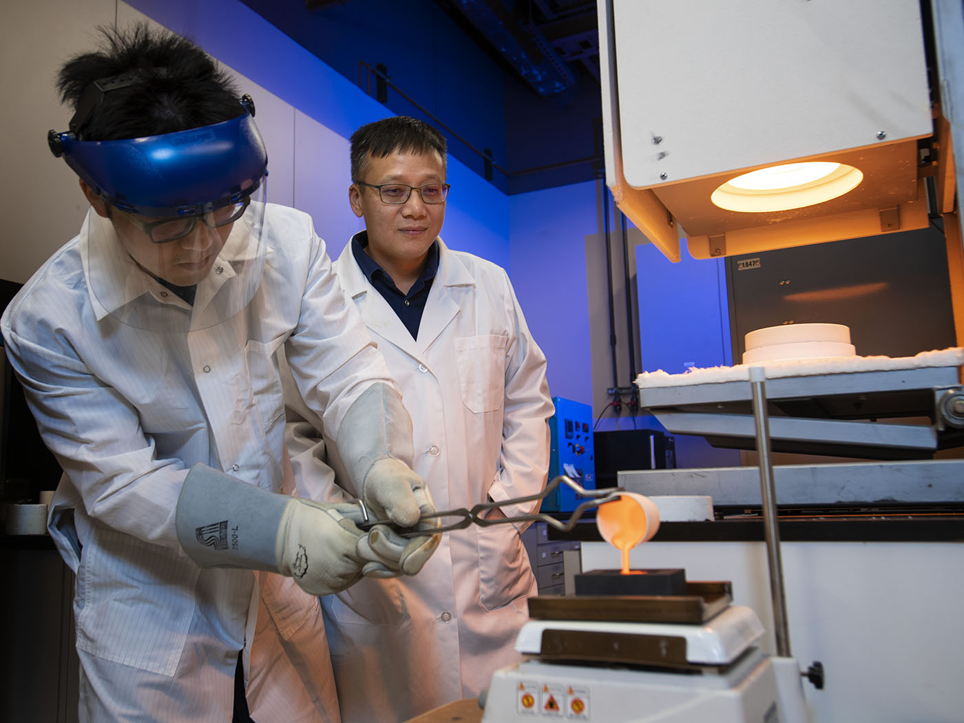 Ph.D. student Po-Hsuen Kuo pours molten glass as Professor Jincheng Du looks on.