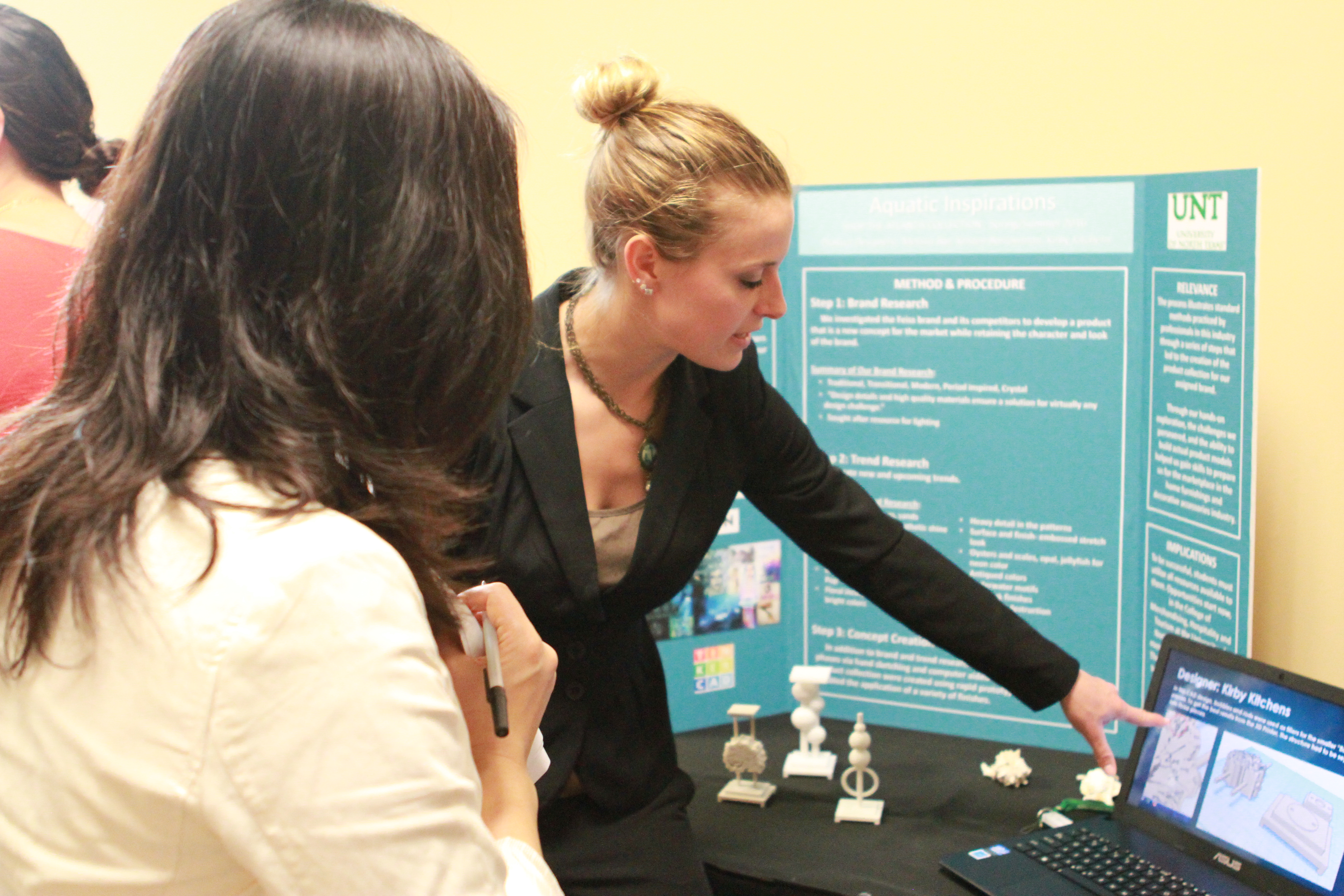 A UNT student shares her research with a judge during the student research competition for the 2015 Consumer Experience Symposium. Photo courtesy of the College of Merchandising, Hospitality and Tourism.