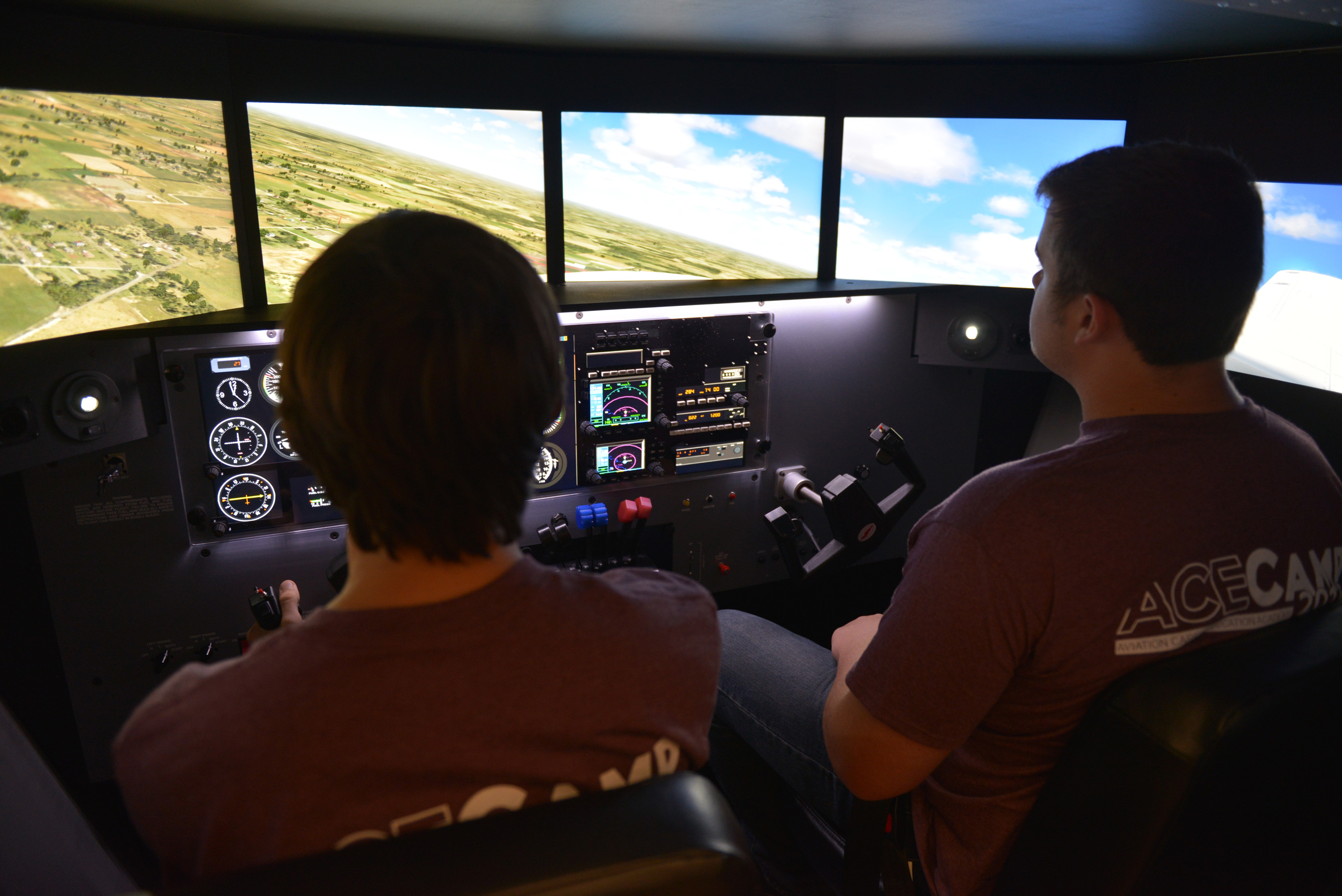 Two high schoolers fly a flight simulator