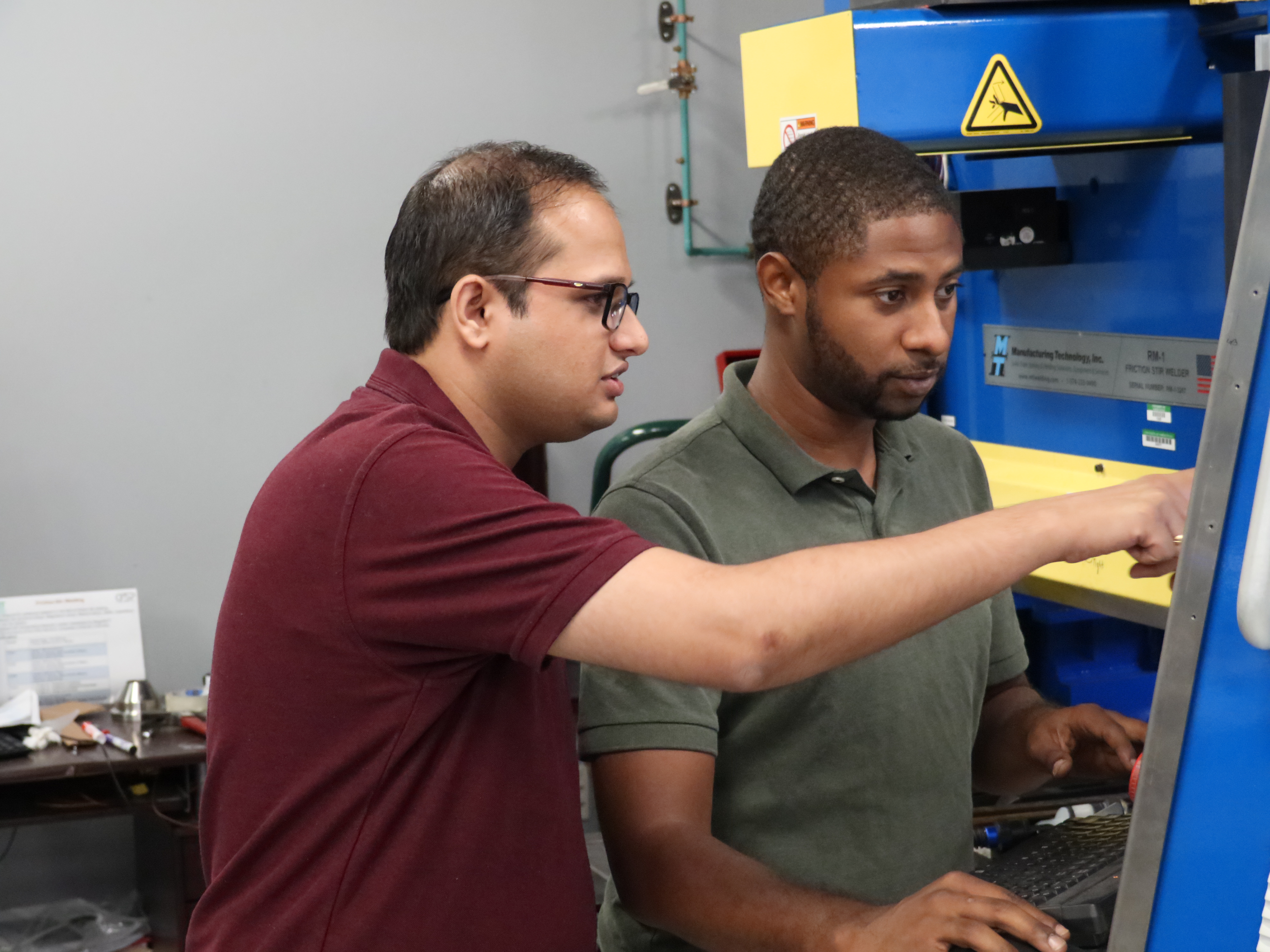 Dr. Saurabh Nene (left) and graduate research assistant Michael Frank monitor the Friction Stir Process